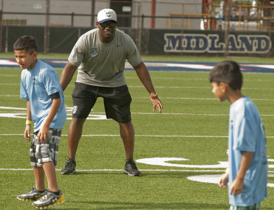 LaDainian Tomlinson works with students as they run football drills Wednesday, 6-17-15, during the LaDainian Tomlinson Preparatory Academy with the Midland Boys and Girls Club at Midland Christian's Mustang Field. Tim Fischer\Reporter-Telegram Photo: Tim Fischer