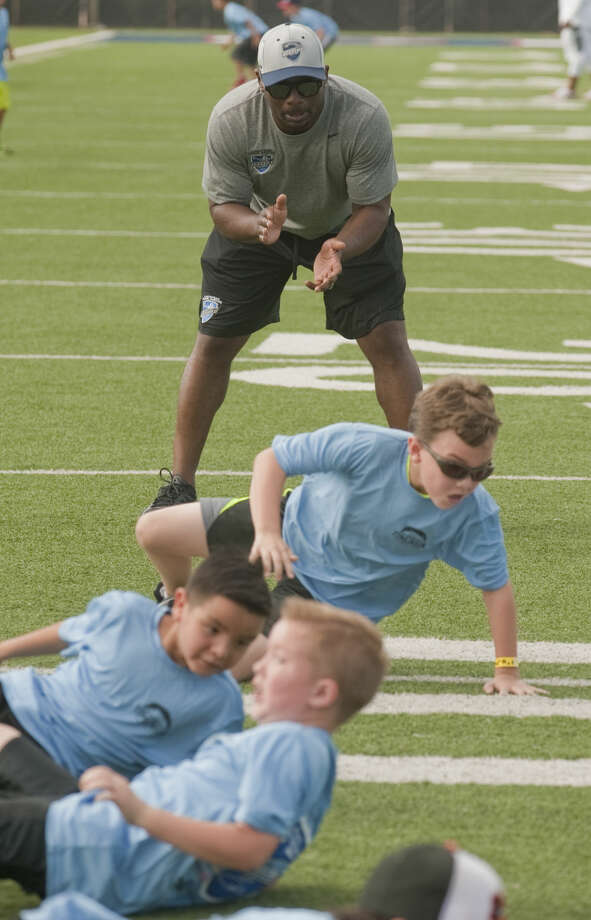 LaDainian Tomlinson encourages students as they run football drills Wednesday, 6-17-15, during the LaDainian Tomlinson Preparatory Academy with Midland Boys and Girls Club at Midland Christian's Mustang Field. Tim Fischer\Reporter-Telegram