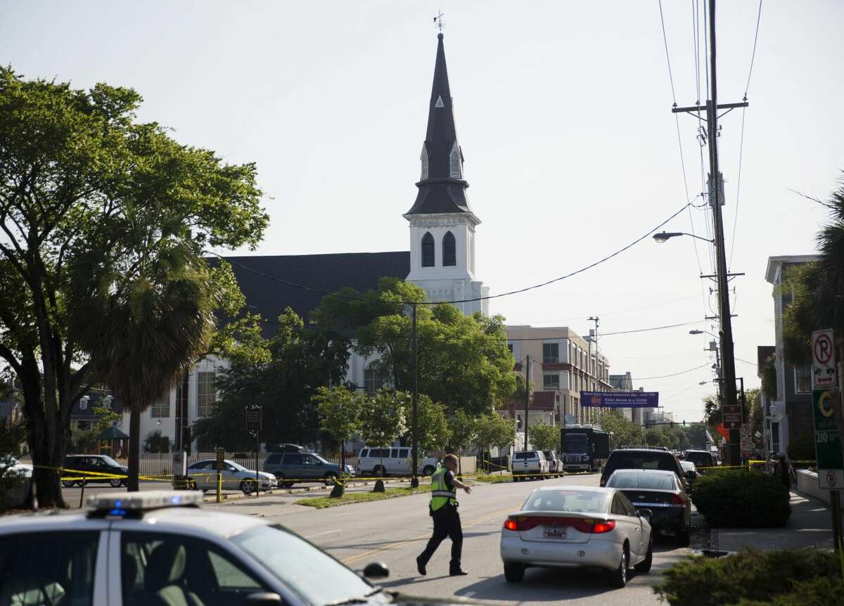 The steeple of Emanuel AME Church rises above the street as a police officer tells a car to move as the area is closed off following Wednesday's shooting, Thursday, June 18, 2015 in Charleston, S.C. (AP Photo/David Goldman)