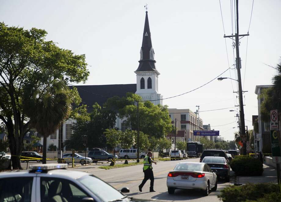 The steeple of Emanuel AME Church rises above the street as a police officer tells a car to move as the area is closed off following Wednesday's shooting, Thursday, June 18, 2015 in Charleston, S.C. (AP Photo/David Goldman) Photo: David Goldman