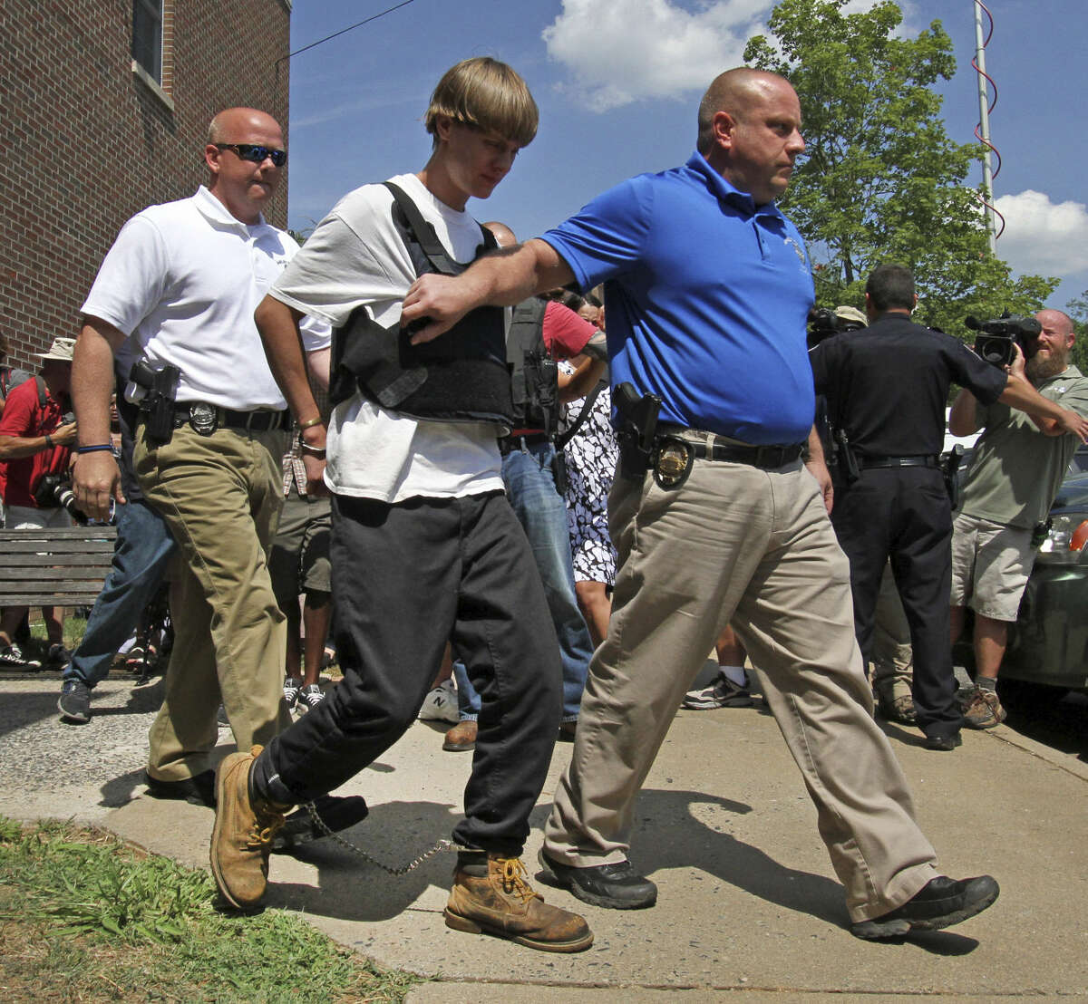 Charleston, S.C., shooting suspect Dylann Storm Roof, second from left, is escorted from the Shelby Police Department in Shelby, N.C., Thursday, June 18, 2015. Roof is a suspect in the shooting of several people Wednesday night at the historic The Emanuel African Methodist Episcopal Church in Charleston, S.C. (AP Photo/Chuck Burton)