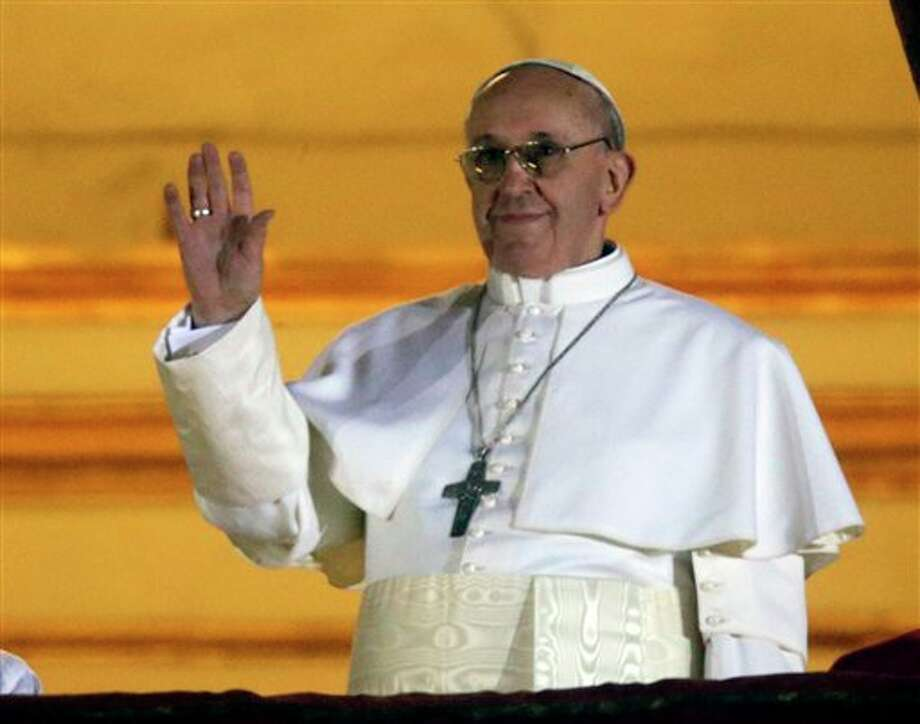 Pope Francis waves to the crowd from the central balcony of St. Peter's Basilica at the Vatican, Wednesday, March 13, 2013. Cardinal Jorge Bergoglio who chose the name of Francis is the 266th pontiff of the Roman Catholic Church. (AP Photo/Gregorio Borgia) Photo: Gregorio Borgia / AP2013