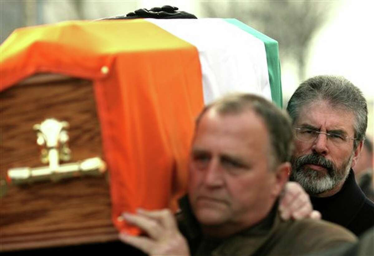 FILE - In this Tuesday Feb. 19, 2008 file photo, Sinn Fein President Gerry Adams, right, carries the coffin of senior IRA commander Brendan Hughes, in west Belfast, Northern Ireland. Police in Northern Ireland arrested Sinn Fein party leader Gerry Adams on Wednesday over his alleged involvement in the Irish Republican Army's 1972 abduction, killing and secret burial of a Belfast widow. Adams, 65, confirmed his own arrest in a prepared statement and described it as a voluntary, prearranged interview. Police long had been expected to question Adams about the killing of Jean McConville, a 38-year-old mother of 10 whom the IRA killed with a single gunshot to the head as an alleged spy. Adams was implicated in the killing by two IRA veterans, who gave taped interviews to researchers for a Boston College history archive on the four-decade Northern Ireland conflict. Belfast police waged a two-year legal fight in the United States to acquire the interviews, parts of which already were published after the 2008 death of one IRA interviewee, Brendan Hughes. Boston College immediately handed over the Hughes tapes. The college and researchers fought unsuccessfully to avoid handover tapes of the second IRA interviewee, Dolours Price, who died last year. Both Hughes and Price agreed to be interviewed on condition that their contents were kept confidential until their deaths. (AP Photo/Peter Morrison, file)