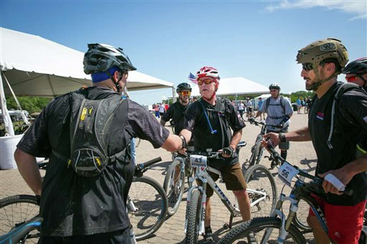 Former President George W. Bush greets participants during the second day of a three-day, 100-kilometer mountain bike ride with 16 wounded veterans Friday, May 2, 2014, in Crawford, Texas. (AP Photo/George W. Bush Presidential Center, Paul Morse)