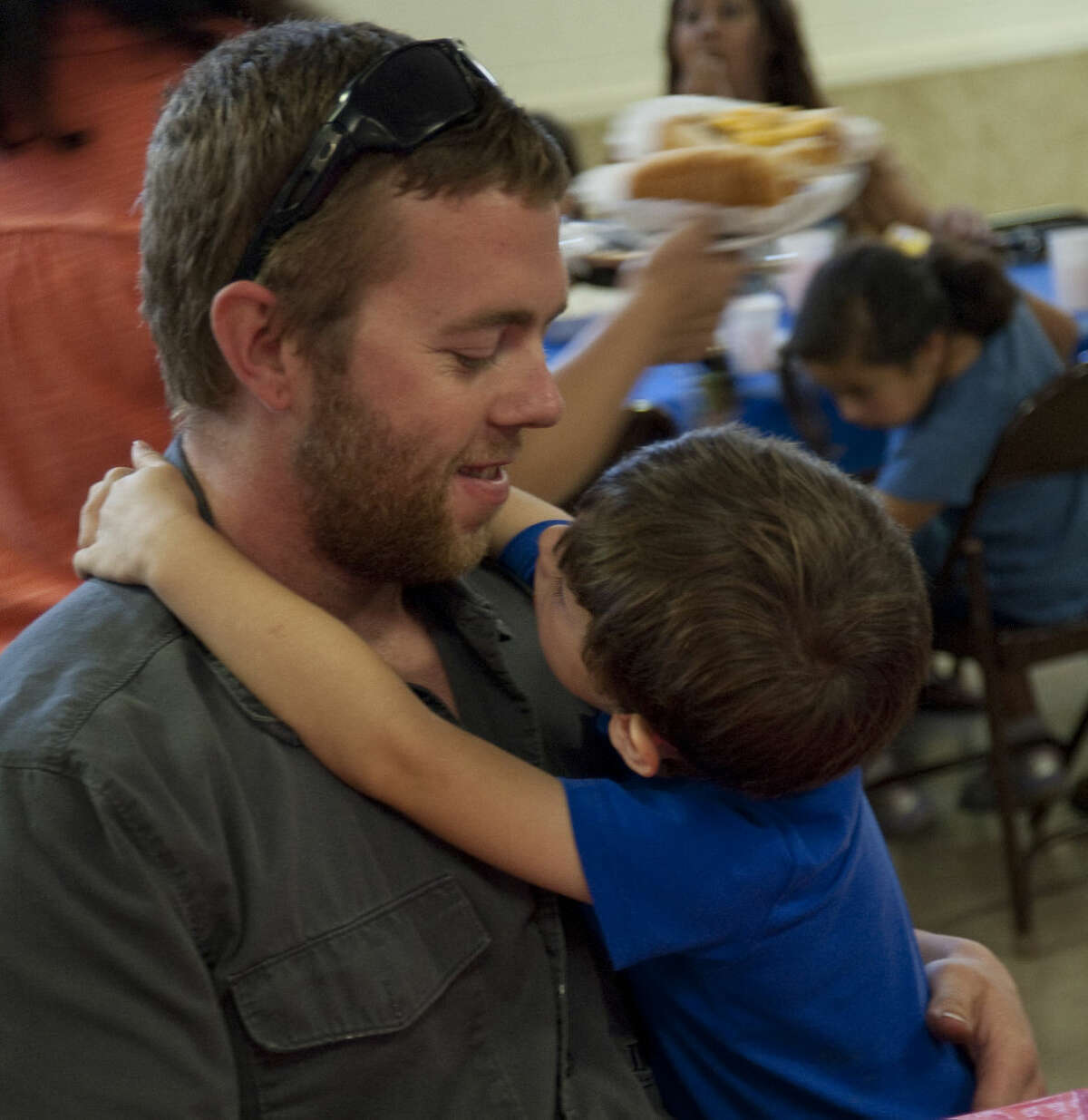 Jake Dolen gets a hug from his son, Braddox Putnam Friday at the Camp Fire USA Father's Day luncheon.