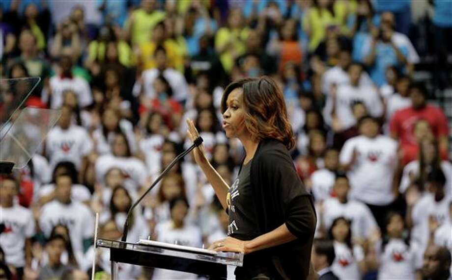 First lady Michelle Obama leads high school students in a pledge for higher education during College Signing Day, an annual celebration of San Antonio high school seniors committing themselves to higher education, Friday, May 2, 2014, in San Antonio. (AP Photo/Eric Gay) Photo: Eric Gay / AP