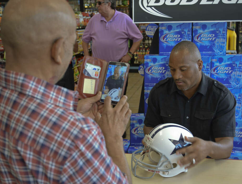 Joe Samarripa takes a picture of former Dallas Cowboys cornerback Larry Brown as he autographs a helmet Wednesday, June 24, at the Stripes on Rankin Hwy and Interstate 20 as the store reopens selling Sunoco gas, the gas of NASCAR. Tim Fischer\Reporter-Telegram Photo: Tim Fischer