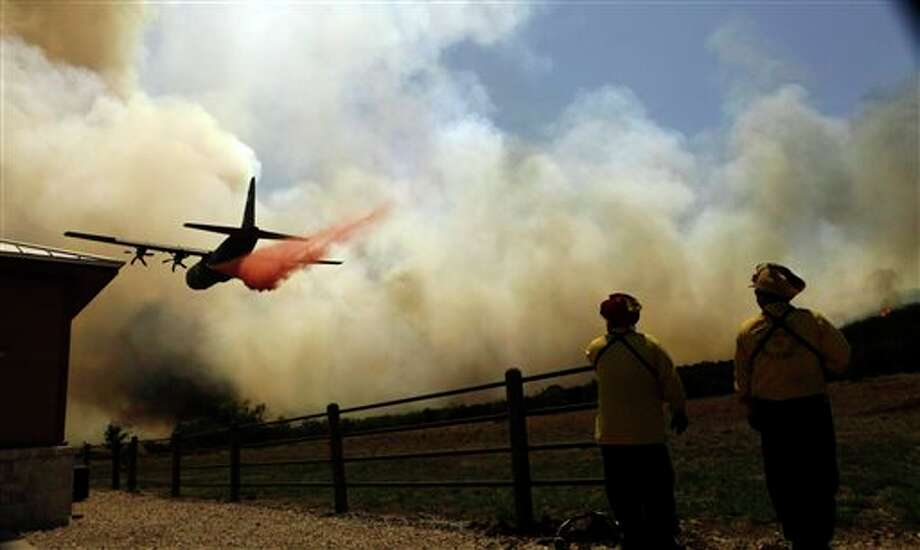 This April 19, 2011 file photo shows firefighters looking on as an air tanker makes a pass over a wildfire near Possum Kingdom, Texas. A federal auditing agency has upheld a challenge Wednesday April 2, 2014 to a U.S. Forest Service contract for two next-generation air tankers to fight wildfires. But what that means for the federal air tanker fleet this summer is not yet clear. The Government Accountability Office recommended the Forest Service either bolster its reasons for awarding the contract to Neptune Aviation Services in Montana, or start the bid process over. The Forest Servce says it is evaluating the recommendations. (AP Photo/LM Otero) Photo: LM Otero / AP