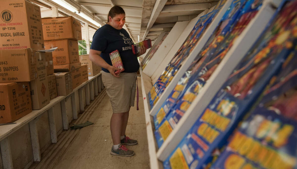 Marissa Rodriquez helps put fireworks on the stands Tuesday, 6-23-15, as she and others prep Mr. W Fireworks stand off S. Big Spring for sales starting today. Tim Fischer\Reporter-Telegram