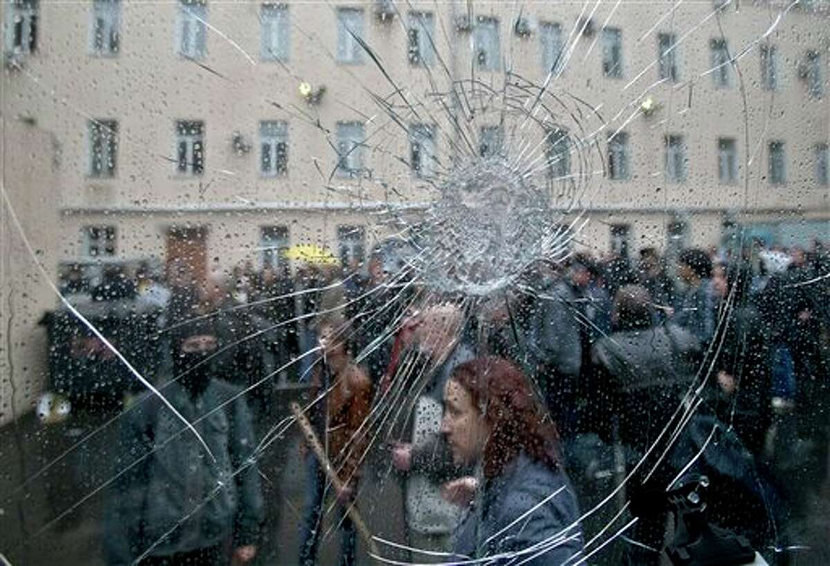 Pro-Russian protesters, seen through the cracked window of a police van, stand in the grounds of a police station in Odessa, Ukraine, Sunday, May 4, 2014. Several prisoners that were detained during clashes that erupted Friday between pro-Russians and government supporters in the key port on the Black Sea coast were released under the pressure of protesters that broke into a local police station and received a hero's welcome by crowds. (AP Photo/Vadim Ghirda)