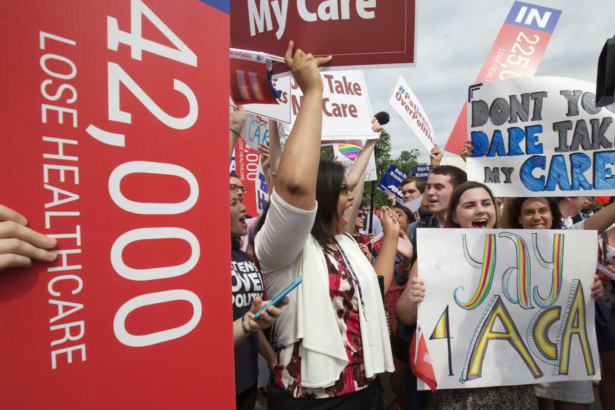 """Jessica Ellis, right, with """"yay 4 ACA"""" sign, and other supporters of the Affordable Care Act, react with cheers as the opinion for health care is reported outside of the Supreme Court in Washington,Thursday June 25, 2015."""