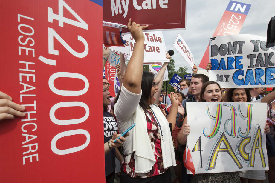 "Jessica Ellis, right, with ""yay 4 ACA"" sign, and other supporters of the Affordable Care Act, react with cheers as the opinion for health care is reported outside of the Supreme Court in Washington,Thursday June 25, 2015. Photo: Jacquelyn Martin"