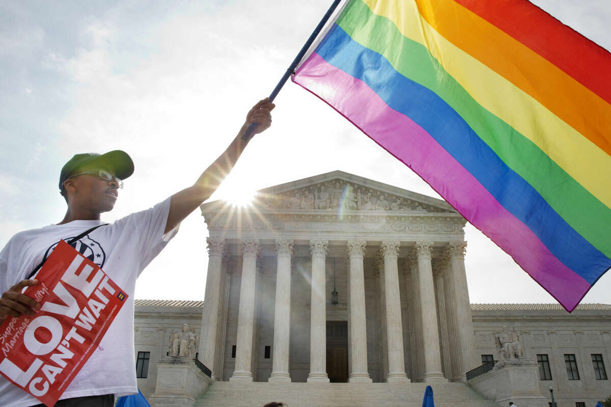 Carlos McKnight of Washington, waves a flag in support of gay marriage outside of the Supreme Court in Washington, Friday June 26, 2015. This photo was taken shortly before a majority of the court's justices ruled that state gay marriage bans were unconstitutional. (AP Photo/Jacquelyn Martin)