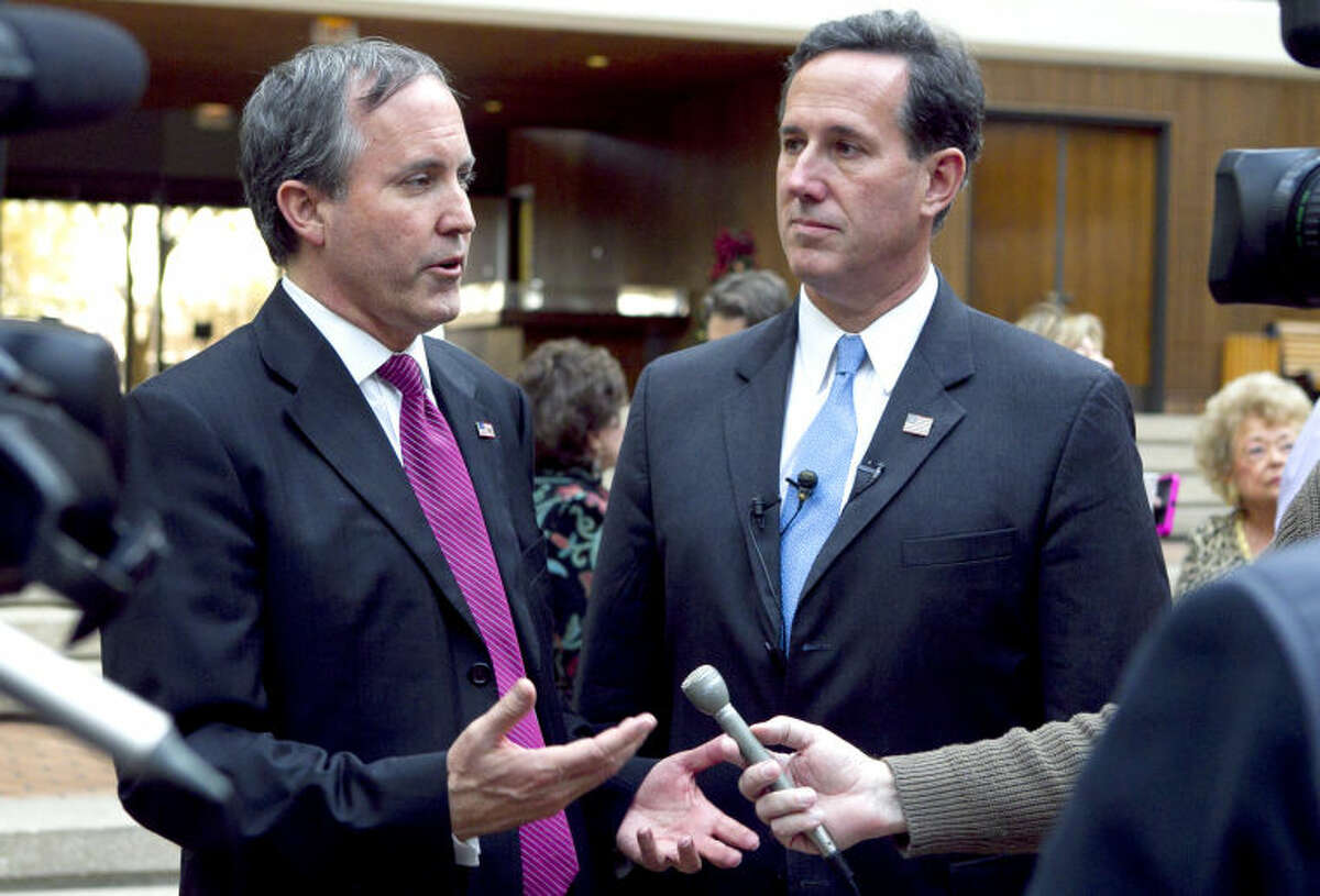 Attorney General candidate Ken Paxton (left) and Sen. Rick Santorum (right) speak to the media during a meet and greet event in the ClayDesta lobby last year. James Durbin/Reporter-Telegram