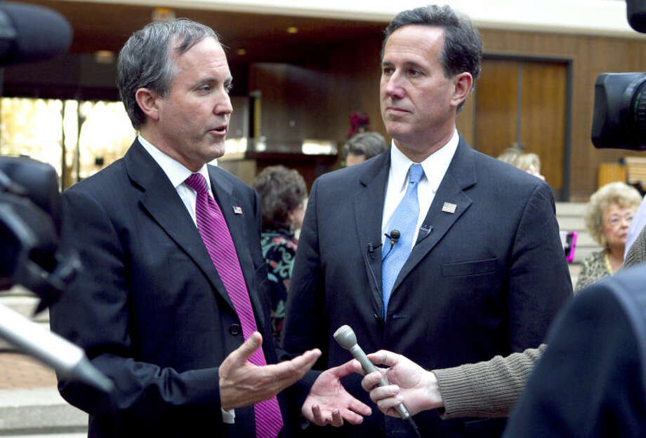 Attorney General candidate Ken Paxton (left) and Sen. Rick Santorum (right) speak to the media during a meet and greet event in the ClayDesta lobby last year. James Durbin/Reporter-Telegram Photo: JAMES DURBIN