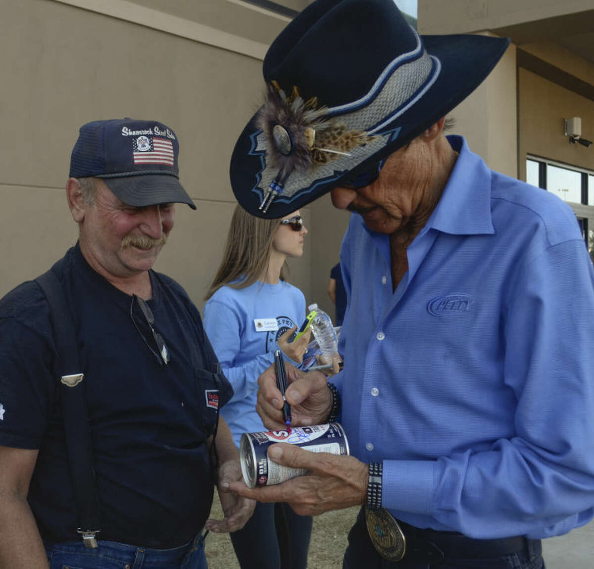 Richard Petty signs a STP oil can for Mike Barrett Monday after flying in to meet up with his son, Kyle Petty, who rode into town with 200 other motorcycle riders on a cross country trip to raise money for Victory Junction Camp on the Kyle Petty Charity Ride. Tim Fischer\Reporter-Telegram