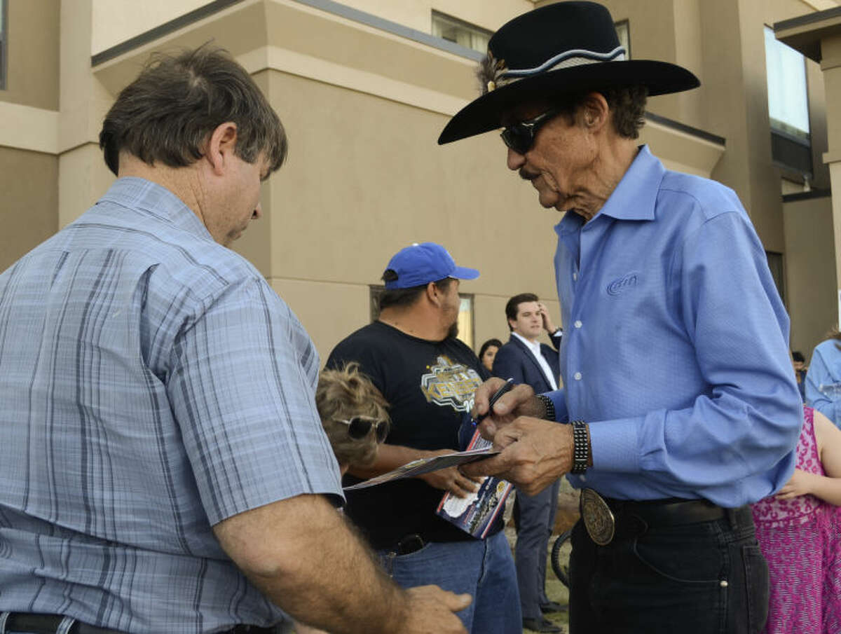 Richard Petty signs autographs Monday after flying in to meet up with his son, Kyle Petty, who rode into town with 200 other motorcycle riders on a cross country trip to raise money for Victory Junction Camp on the Kyle Petty Charity Ride. Tim Fischer\Reporter-Telegram