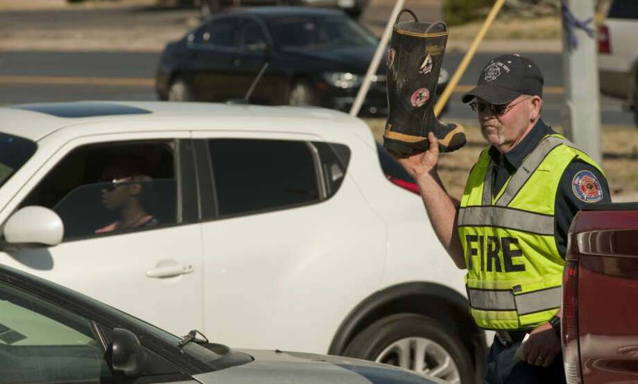 Midland Fire Department Driver Gary Wade carries his boot between cars Wednesday as the Midland Fire Department kicks off this years Fill the Boot campaign to raise money for Muscular Dystrophy. Tim Fischer\Reporter-Telegram Photo: Tim Fischer