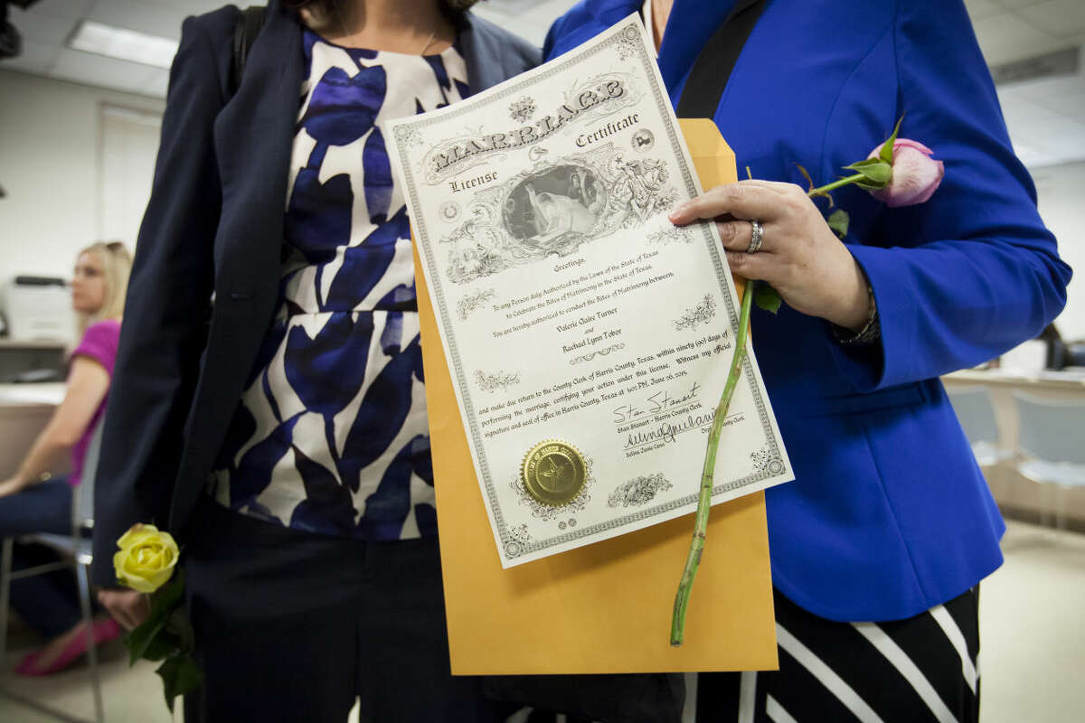 Valerie Turner and Rachael Tobor show their certificate after they were the first couple to get handed their marriage license at the Harris County Courthouse in Houston, June 26, 2015. In a long-sought victory for the gay rights movement, the Supreme Court ruled Friday that the Constitution guarantees a nationwide right to same-sex marriage. (Michael Stravato/The New York Times)