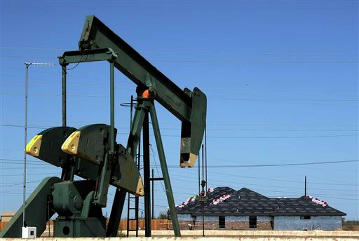 In this Monday, Sept. 23, 2013 photo, a pump jack works beside the site of new home construction, in Midland, Texas. The West Texas town is in the middle of an oil boom with thousands of workers in need of housing. (AP Photo/Pat Sullivan)