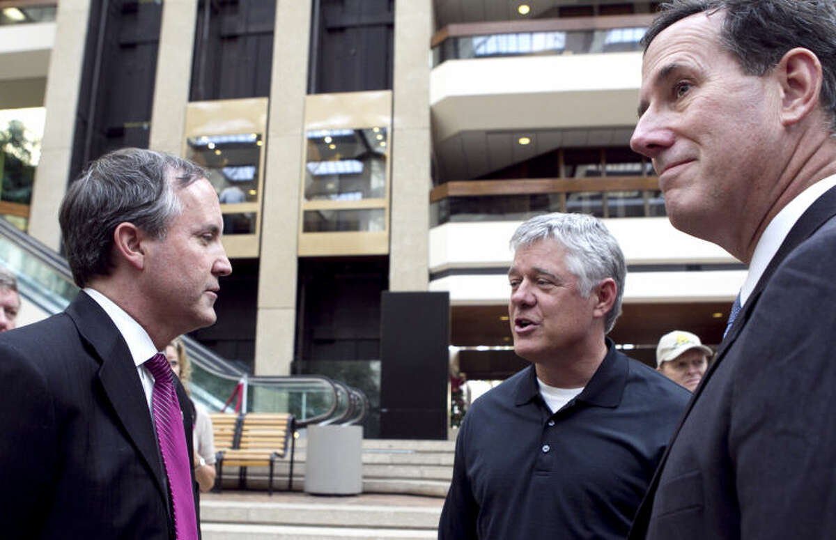 Then-Attorney General candidate Ken Paxton (left) speaks with Douglass Robison (center), president of EXL Petroleum, along with Sen. Rick Santorum (right) during a meet and greet in the ClayDesta lobby in 2013.