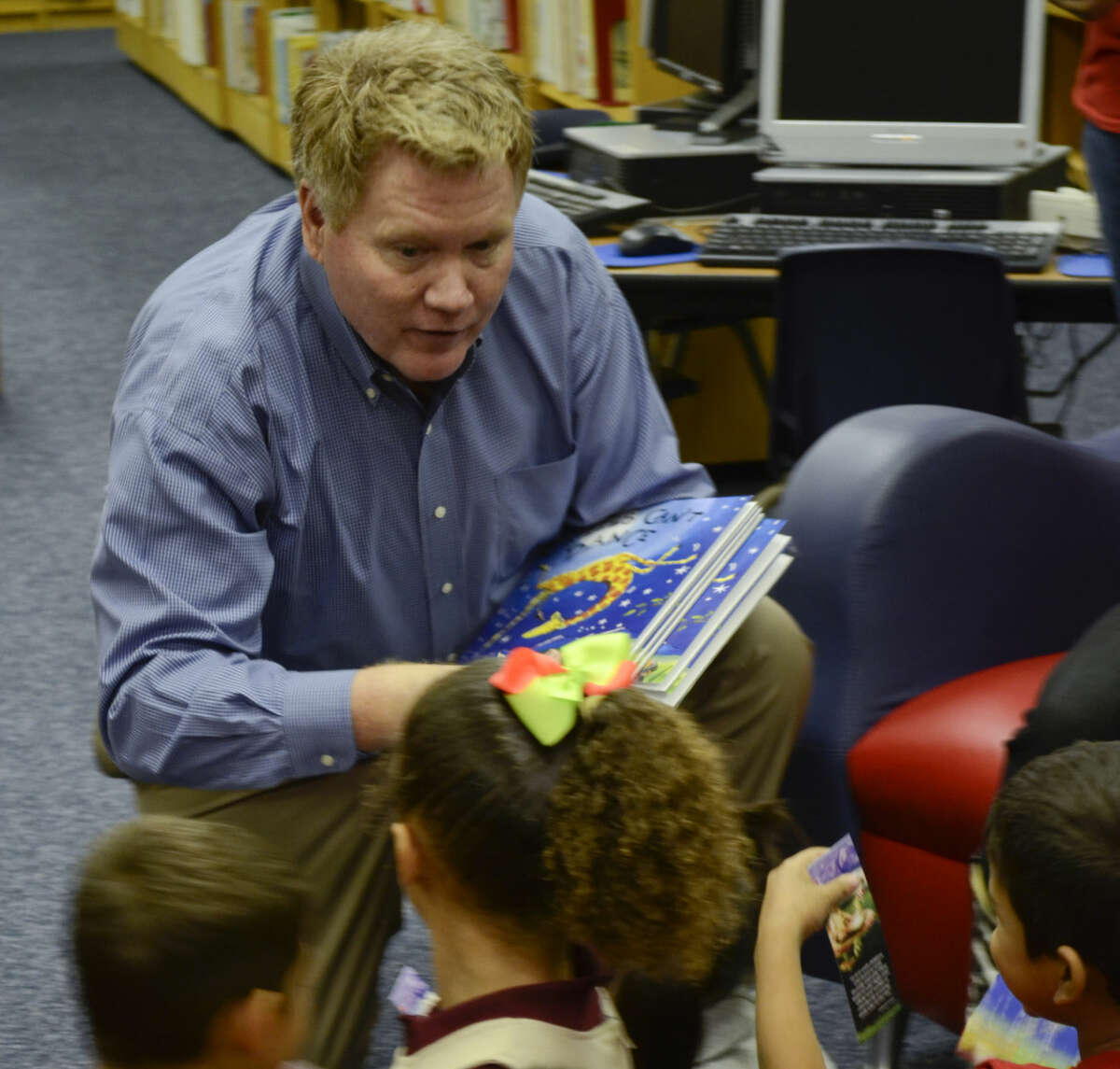 """Publisher Mike Distelhorst hands out copies of """"Giraffes Can't Dance"""" to first-graders at Crockett Elementary in September 2013 as part of Project Literacy. Distelhorst will be leaving the Reporter-Telegram next week for a newspaper group in North Carolina."""