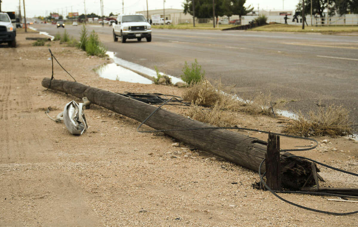 Storms that blew through early Tuesday, 6-30-15, knocked down power poles on S. Midkiff leaving many businesses and homes without phones and internet. Tim Fischer\Reporter-Telegram
