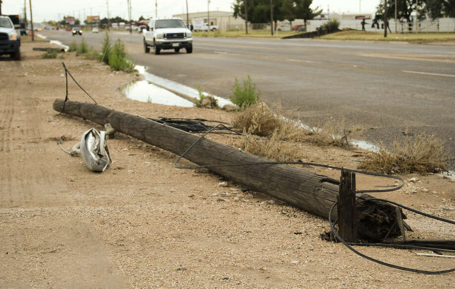 Storms that blew through early Tuesday, 6-30-15, knocked down power poles on S. Midkiff leaving many businesses and homes without phones and internet. Tim Fischer\Reporter-Telegram Photo: Tim Fischer