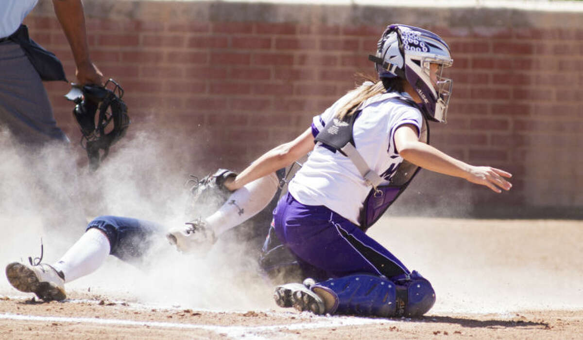Midland catcher Courtney Warren tags out Richland's Maddi Holcomb during the Bulldogs' 2-0 victory against the Rebels in the UIL Softball Regional Quarterfinals on Friday at Plains Capital Park in Lubbock.