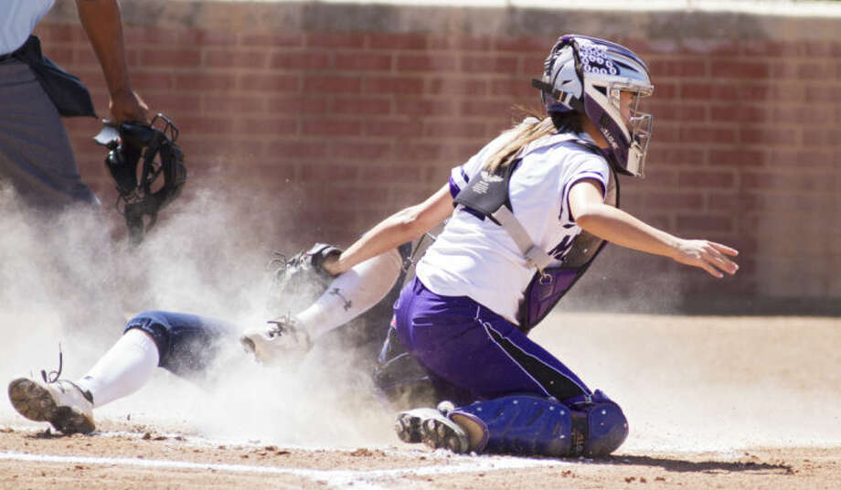 Midland catcher Courtney Warren tags out Richland's Maddi Holcomb during the Bulldogs' 2-0 victory against the Rebels in the UIL Softball Regional Quarterfinals on Friday at Plains Capital Park in Lubbock. Photo: Brad Tollefson