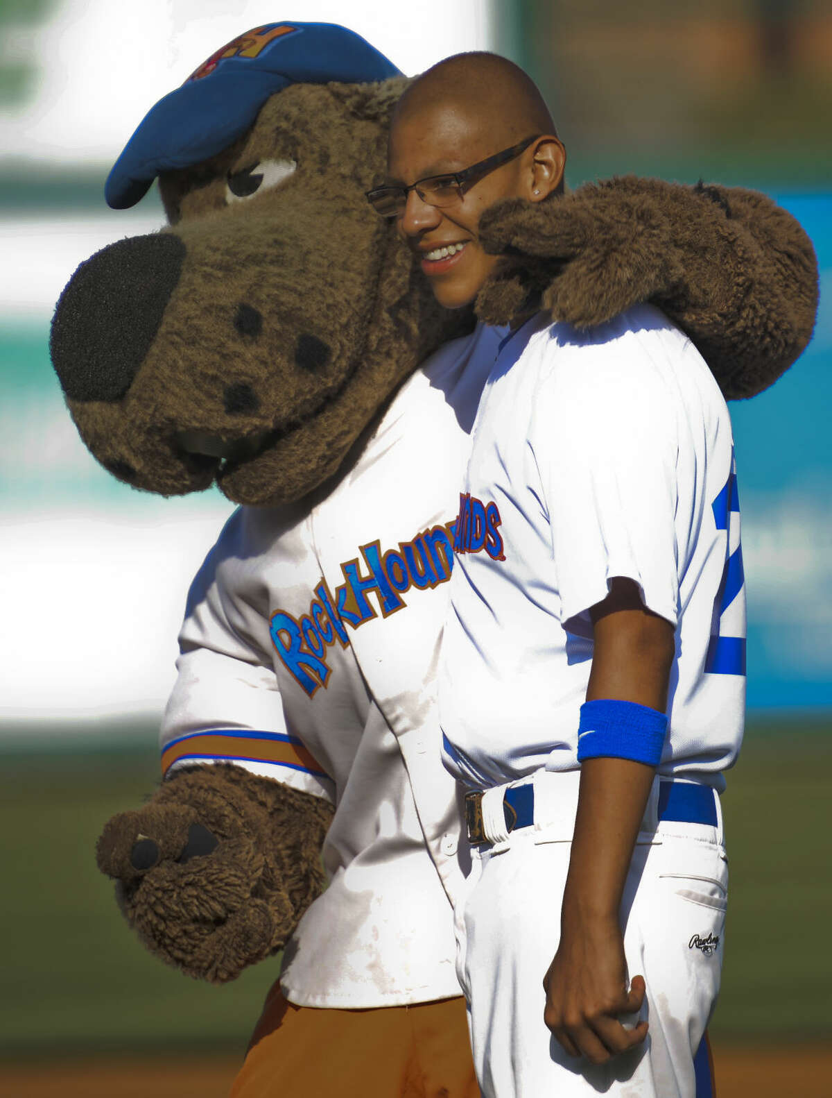Marcelino Rodriguez, 15, is the newest player for the RockHounds Friday 7-3-15, gets a hug from Rocky before the game. Tim Fischer\Reporter-Telegram