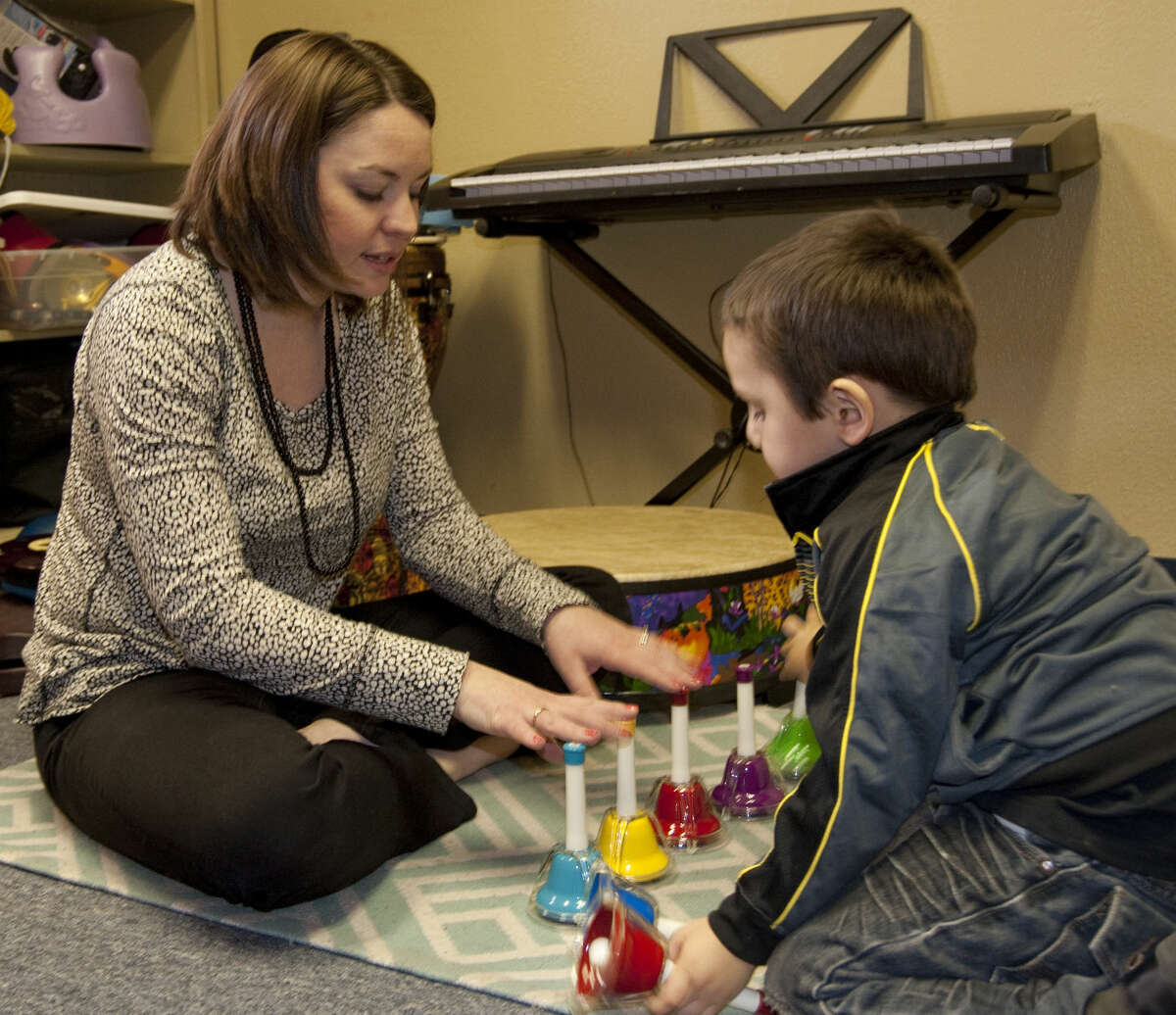 Kayla Minchew uses music with Demetrio Baeza as part of his therapy to learn and use new words. Tim Fischer\Reporter-Telegram