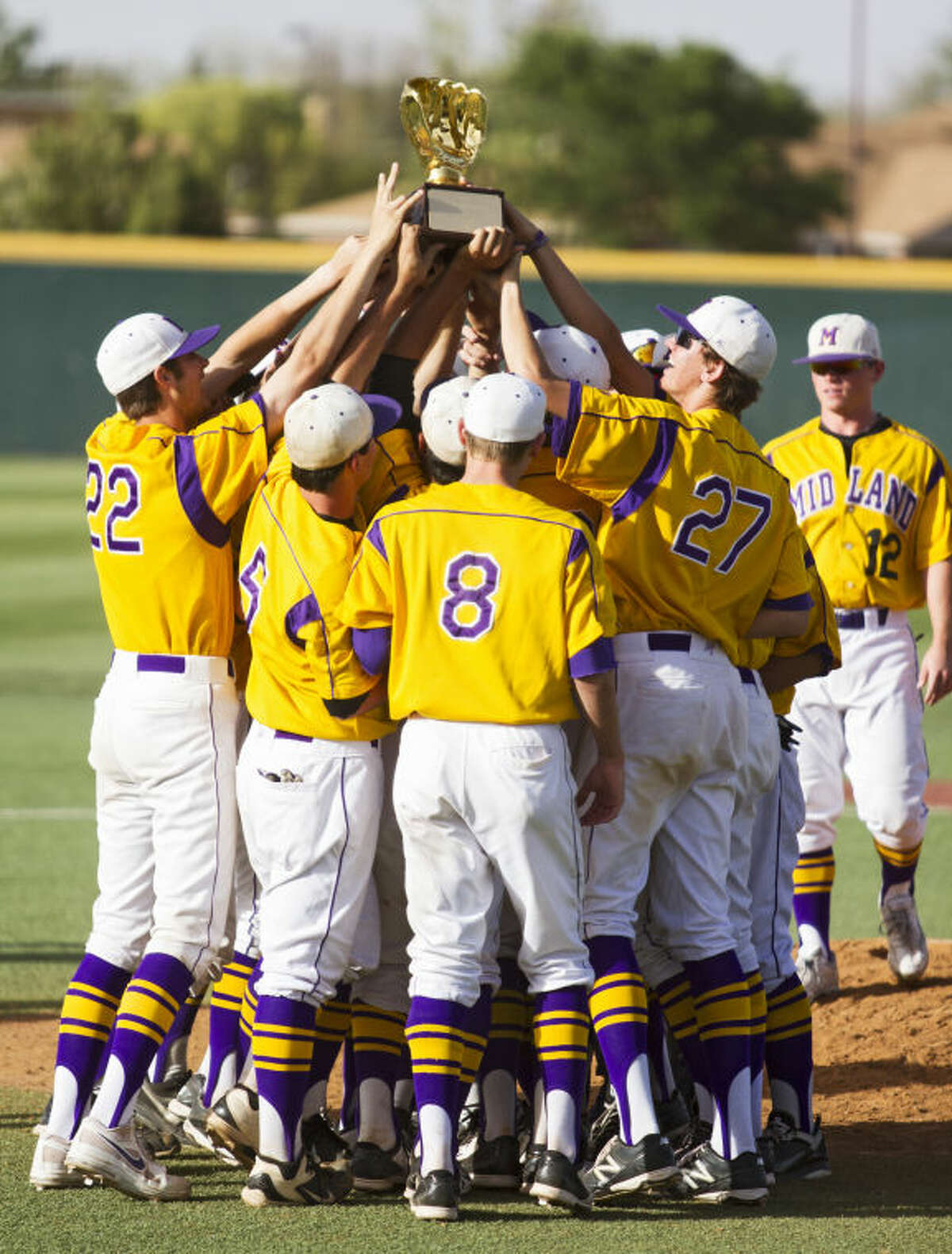 Midland High players hold up the Class 5A Area Trophy after the Bulldogs' 16-14 victory against Richland in the UIL Area Championship on Saturday at Hays Field in Lubbock.