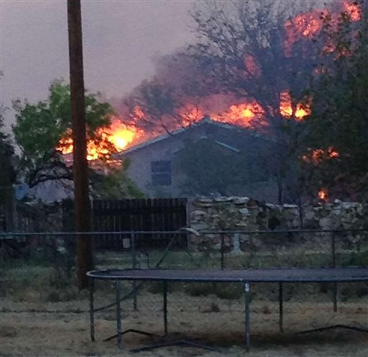 In this Sunday, May 11, 2014 photo provided by the Texas Department of Public Safety, a wildfire burns near Fritch, Texas. The wildfire has led to evacuations and road closures and has destroyed dozens of homes. (AP Photo/Texas Department of Public Safety, Chris Ray)