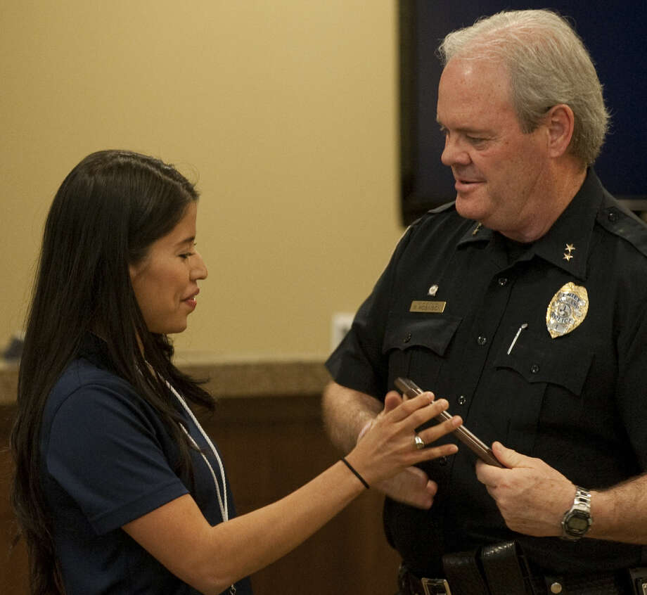 Eliana Samaniego presents Chief Price Robinson with an award in April for MPD's work with the community during the National Crime Victims' Rights Week program. Tim Fischer\Reporter-Telegram Photo: Tim Fischer