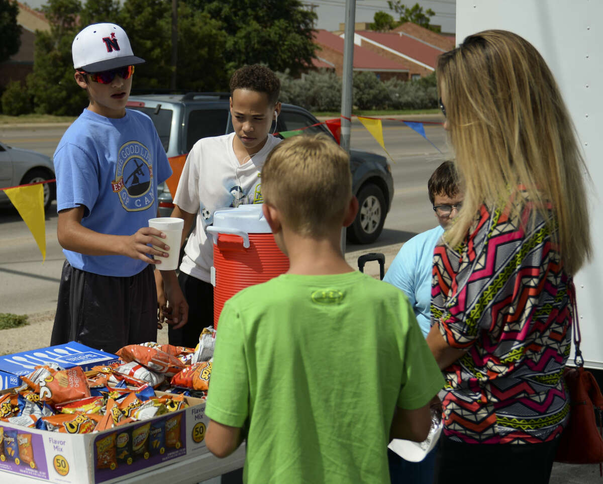 Jonathan Aguirre and others serve up freshmade lemonade to Stephanie Fife and her son Kyler Wednesday 7-8-15, as they and other junior high students hold a lemonade sale and car wash to raise money for Opportunity Camp. Tim Fischer\Reporter-Telegram