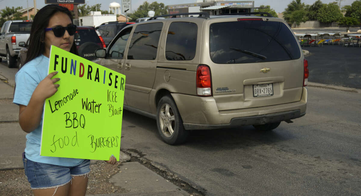 Katy Rodriguez holds a sign to advertise for Unlock Ministries as she and others serve up freshmade lemonade Wednesday 7-8-15, as they and other junior high students hold a lemonade sale and car wash to raise money for Opportunity Camp. Tim Fischer\Reporter-Telegram