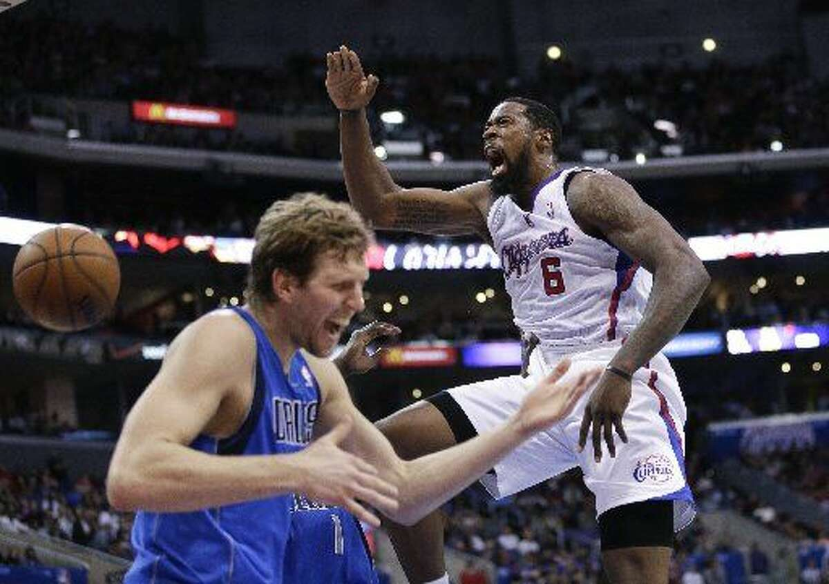 In this April 3, 2014, file photo, Los Angeles Clippers' DeAndre Jordan, right, screams after making a dunk in front of Dallas Mavericks' Dirk Nowitzki during the first half of an NBA basketball game in Los Angeles. The fallout from DeAndre Jordan's decision to spurn the Dallas Mavericks and stay with the Los Angeles Clippers continued reverberating through the NBA on Thursday, July 9, 2015, the first day that teams and players could officially do business in the new league year. (AP Photo/Jae C. Hong, File)