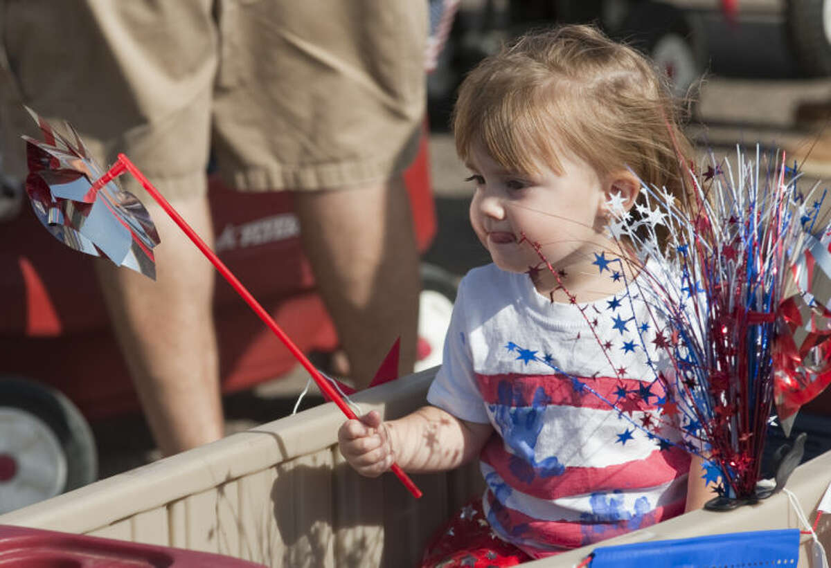 Layla Stone, 2, rides in a cart as she and others participate in the 2014 July 4th Children's Parade. Tim Fischer\Reporter-Telegram