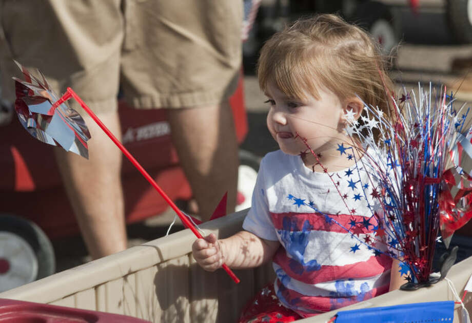 Layla Stone, 2, rides in a cart as she and others participate in the 2014 July 4th Children's Parade. Tim Fischer\Reporter-Telegram Photo: Tim Fischer