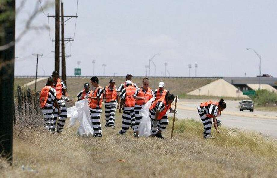 Members of the inmate work crew work to clean up a section of road at the intersection of State Highways 158 and 191. Reporter-Telegram file photo.
