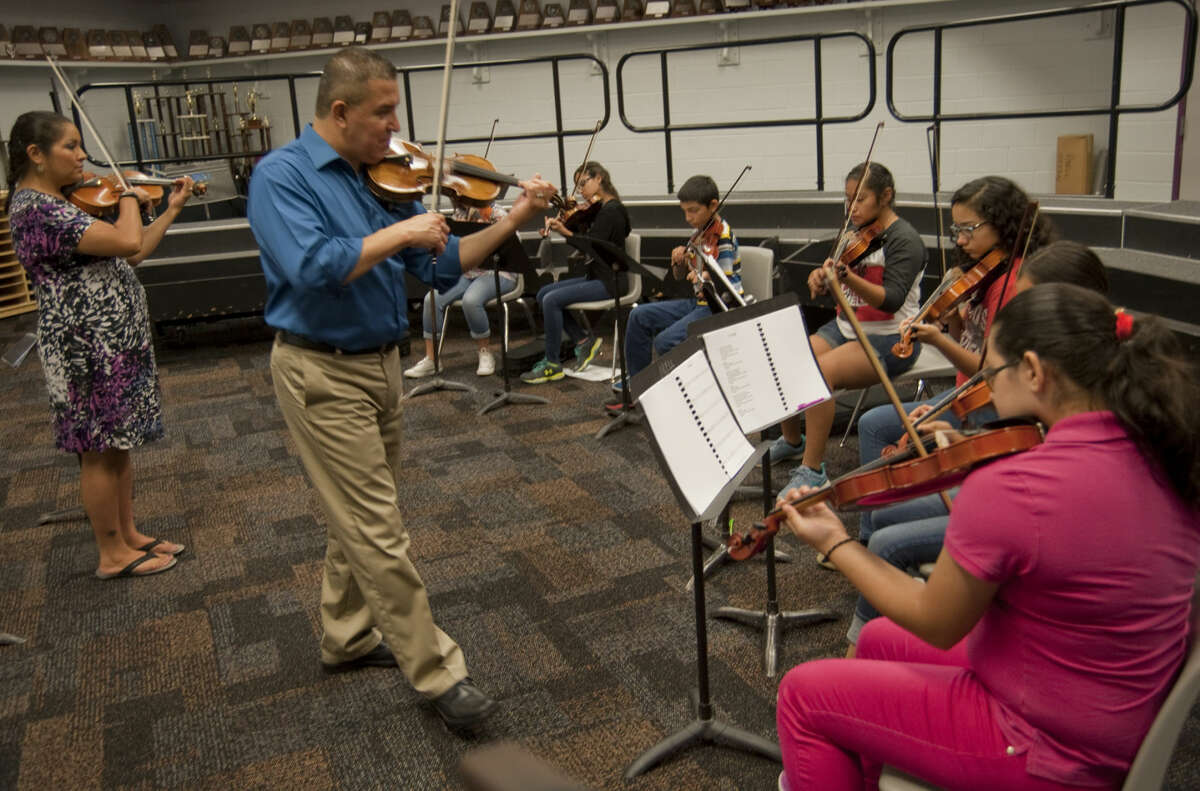 Jose Santiago and Monica Trujillo work with violin students Wednesday, 6-10-15, during the mariachi workshop at Abell Junior High, put on by Midland Hispanic Cultural Center. Tim Fischer\Reporter-Telegram
