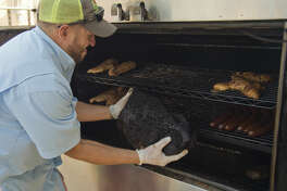 Derel Webb pulls brisket from the rotisserie smoker Thursday 7-9-15, after 20 hours of cooking as he helps get Mac's Bar-B-Q ready for the lunch crowd. Tim Fischer\Reporter-Telegram
