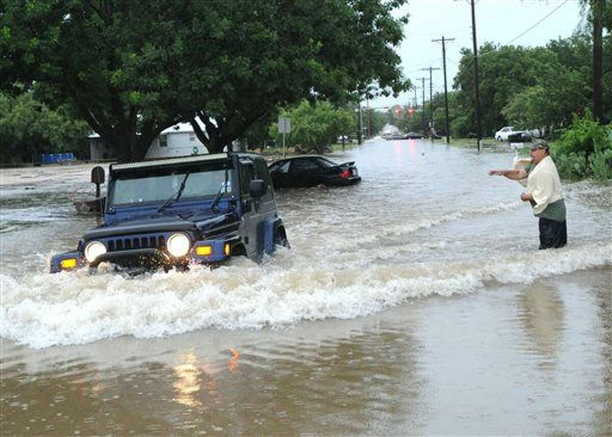 A homeowner throws a rock at a motorist driving through deep water on South 11th Street near Catclaw Creek, as the waves are lapping into the man's garage nearby Tuesday, July 7, 2015, in Abilene, Texas. (Nellie Doneva/The Abilene Reporter-News via AP)