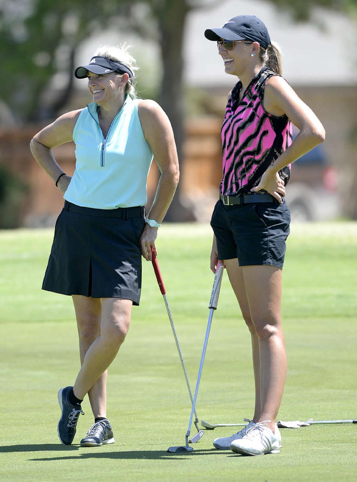 Lia Watson, left, and Danica Weddle, right, make small talk on the 17 green during the Midland Women's City Golf Tournament qualifying round Monday, July 13, 2015, at Green Tree Country Club. James Durbin/Reporter-Telegram