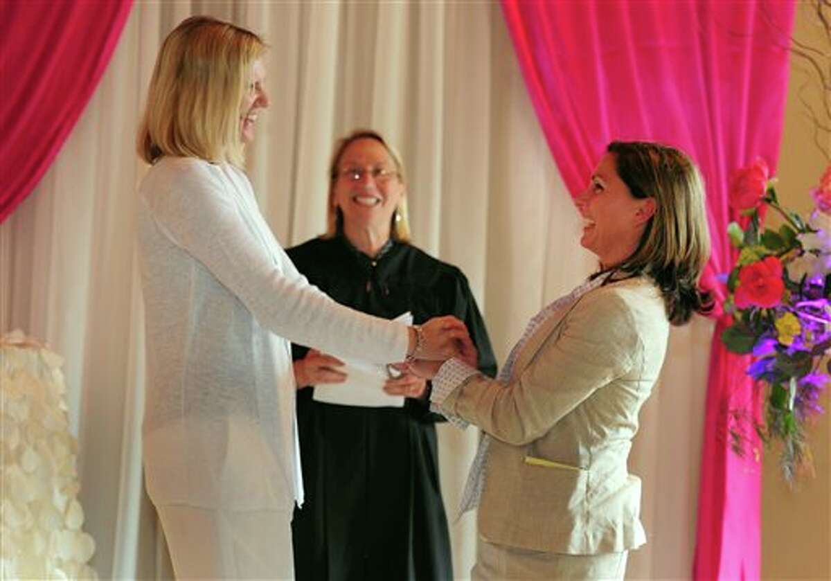 Julie Engbloom, left, and Laurie Brown, right, get married by Judge Beth A. Allen at the Melody Ballroom, Monday, May, 19, 2014, in Portland, Ore. Federal Judge Michael McShane released an opinion on Oregon's Marriage Equality lawsuit that grants gay and lesbian couples the freedom to marry in Oregon. (AP Photo/Steve Dykes)