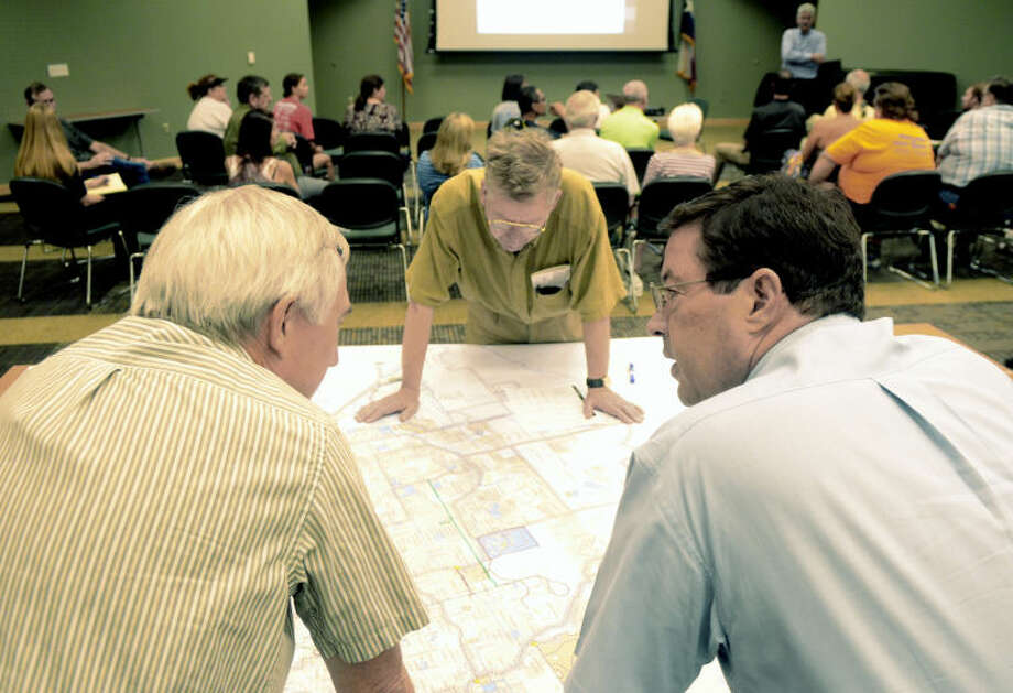 David Ham (left), owner of Peyton's Bikes, George McAlpine (center), and Lourcey Sams (right), chairman of the parks and recreation advisory board, and look over a map during a public meeting to gather input on the city's first Trails Master Plan on Monday in the Carrasco Room of Midland College. James Durbin/Reporter-Telegram Photo: James Durbin