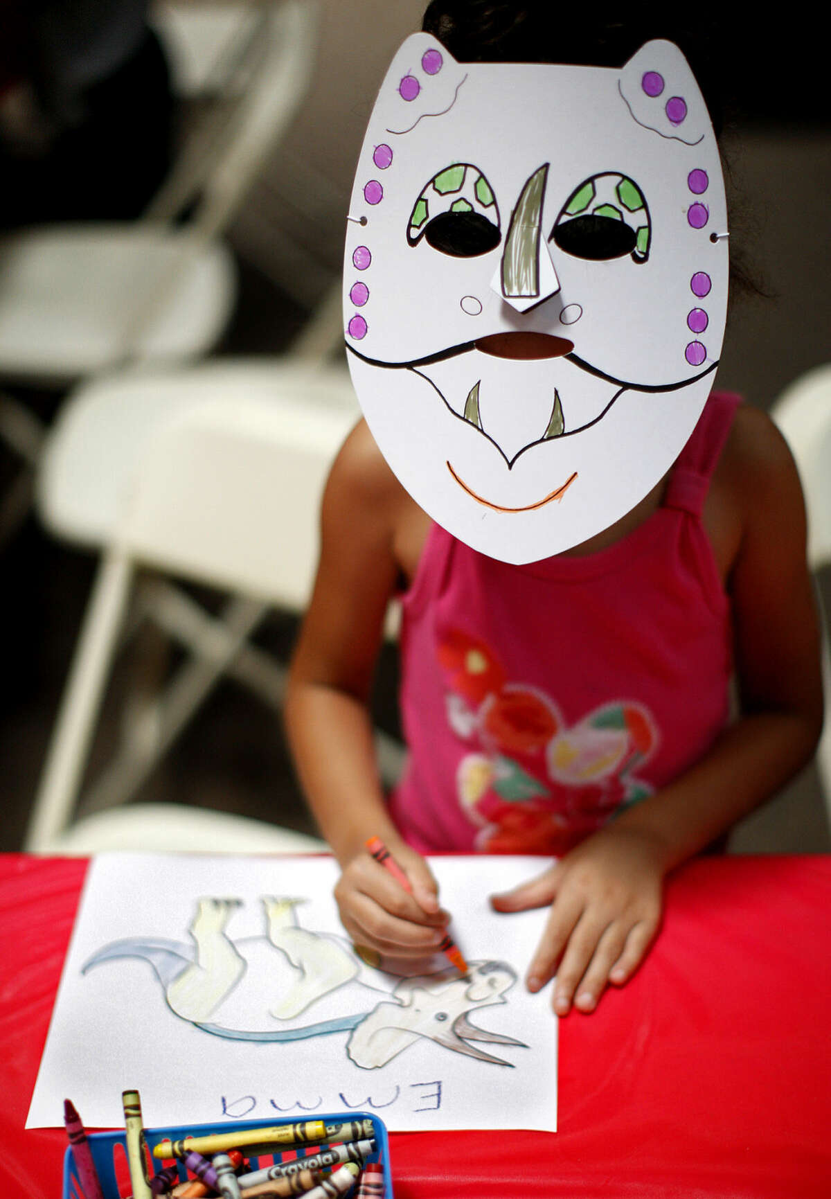 Emma Jackson, age 5, draws a picture of a dinosaur at the Permian Monsters exhibit in the Museum of the Southwest on Saturday, July 11, 2015. James Durbin/Reporter-Telegram