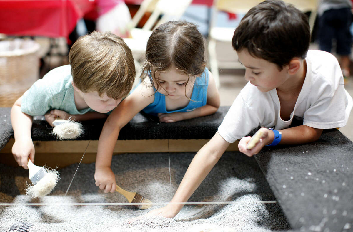 Children excavate fossils at the Permian Monsters exhibit in the Museum of the Southwest on Saturday, July 11, 2015. James Durbin/Reporter-Telegram