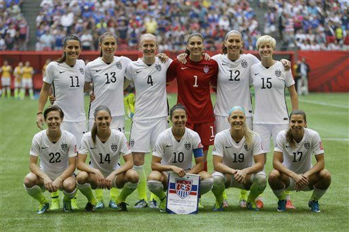 The United States Women's National Team, including goalkeeper Hope Solo (1) and midfielder Carli Lloyd (10) pose for the traditional team photo before beating Japan 5-2 in the the FIFA Women's World Cup soccer championship in Vancouver, British Columbia, Canada, Sunday, July 5, 2015. (AP Photo/Elaine Thompson)